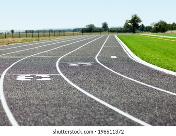 A running track at ground level with a fence and field in the background.