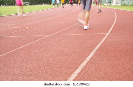 Running track with running legs in sport shorts and jogging shoes