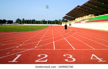 Running track lines with green grass in the stadium on daytime.