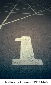 Running track with number one, detail of a running track, with the starting line number one, textured background, sport