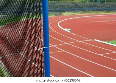 Running track on a old stadium, safety net in focus