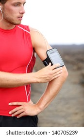 Running training music - runner man listening to music adjusting settings on armband for smartphone. Fit male fitness model working out outside in red sporty outfit.