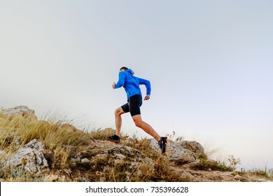 running uphill on stones male athlete runner side view