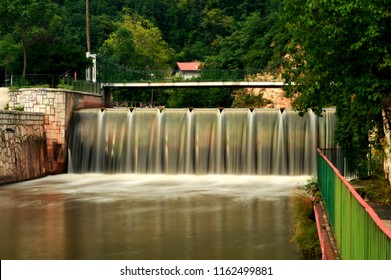 Running water over a city concrete dam on Miljacka river in Sarajevo, Bosnia and Herzegovina. The water is blurred by long exposure.