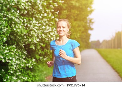 Running woman atletic spotsman trains in the summer park. Outdoor fitness portrait