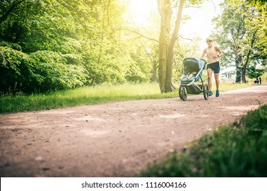 Running woman with baby stroller enjoying summer day in park. Jogging or power walking supermom, active family with baby jogger.