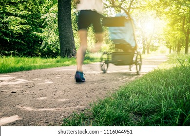 Running woman with baby stroller enjoying summer in park. Jogging or power walking supermom, active family with baby jogger, motion blur.
