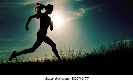 Running woman at dramatic sunset. Sport and freedom concept, toned image