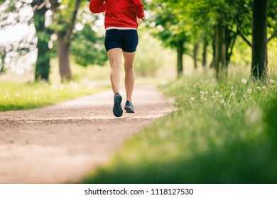 Running woman, enjoying summer day in park. Endurance training, jogging or power walking female athlete, physical activity concept outdoors.