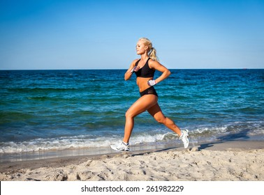 Running woman. Female runner jogging during outdoor workout on beach