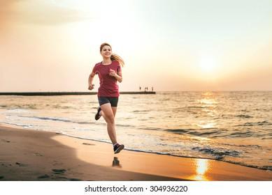 Running woman. Female runner jogging during the sunrise on beach.