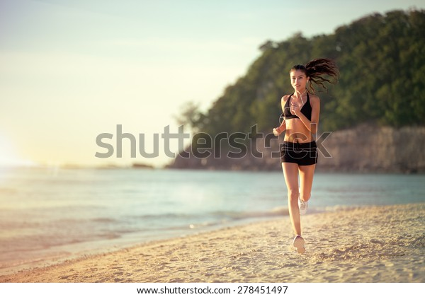 ランニングウーマン、アウトドアでのビーチでの運動中にジョギングする女性ランナー。屋外のフィットネスモデル。