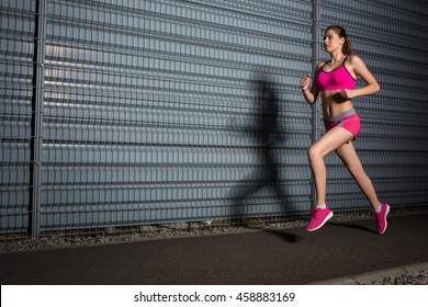 Running woman. jogging against the background of a gray wall