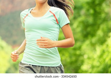 Running Woman Jogging. Midsection of determined woman runneron sunny day. Young female is in sports clothing. Sporty athlete runner is exercising against trees.
