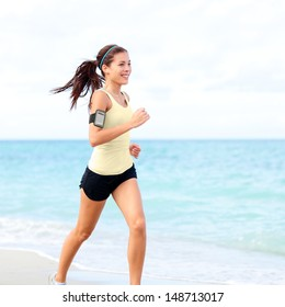 Running woman jogging on beach listening to music in earphones from smart phone mp3 player smartphone armband, Female runner training for marathon on beautiful beach. Mixed race Asian woman.