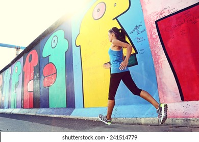 Running woman jogging sightseeing and sightrunning by Berlin Wall, Germany. Female runner training outdoors in city for marathon. Mixed race Asian Caucasian female model.
