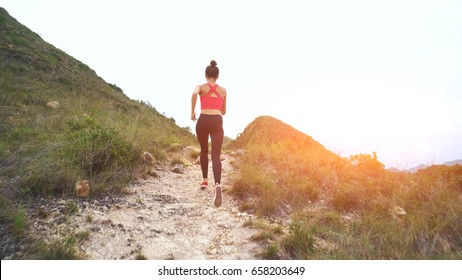 Running woman on mountain road. Sport girl exercising outside in mountains