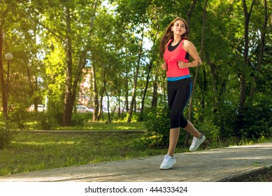 Running woman in park on summer training, girl in sporty clothes.