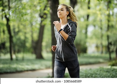 Running woman in park in summer training. Young sport fitness model in sporty running clothes in park.