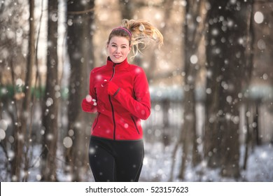 Running woman  in snowy winter park. Winter running exercise. Runner jogging in snow. Young woman fitness model running in a city park