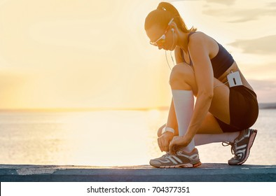 Running woman in sport sunglasses. Female runner before training outdoor workout on beach. Beautiful fit mixed race Fitness model outdoors.