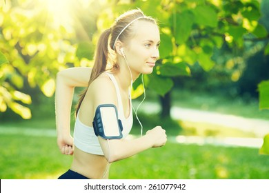 Running woman in summer. Runner is jogging in sunny bright light in the morning park. Female fitness model training and listening music outside in the green summer or spring outdoors. Sport lifestyle.