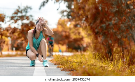 Running woman tying laces of running shoes before jogging through the road in the workout autumn nature park.  Jogger tire after running.  Weight Loss and Healthy Concept