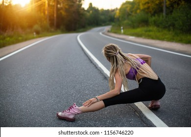Running woman warms up before jogging on the road.
