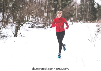 Running woman in winter forest. Trail running