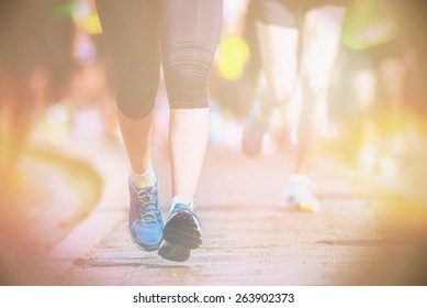 Running womans legs and feet closup during a marathon, filters applied