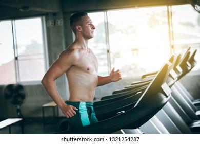 Running . young man running on treadmill at gym