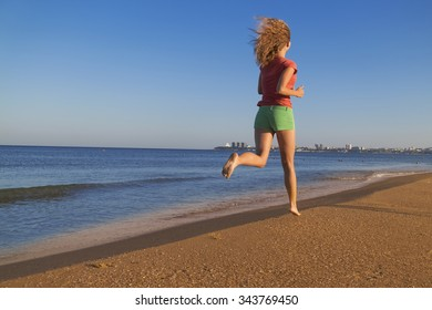 Running young woman. Female runner jogging during outdoor workout on beach.