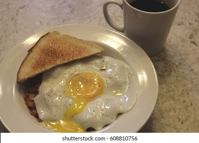 runny egg over hash with toast and black coffee