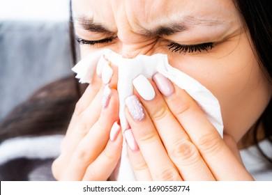 コロナウイルスの鼻水。風邪の症状。アレルギー。鼻水の女。鼻炎。ミニンギスの症状。