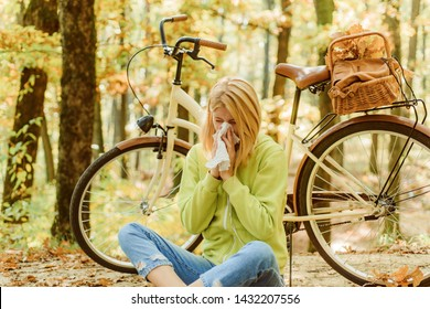 Runny nose remedies. Seasonal allergy. Woman handkerchief sneezing because of allergy. Blonde allergic reaction relax forest. Girl bicycle in nature. Woman bicycle autumn forest suffers from allergy.
