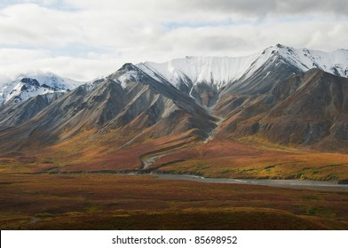 Runoff from the snow covered foothills of the Alaska Range of Mountains feeds into a braided river in the valley below. Denali National Park, Alaska.
