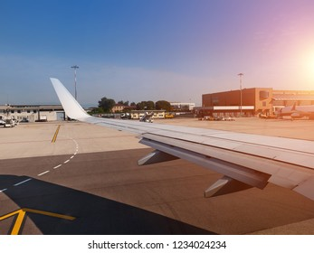 At runway. Aircraft in airport terminal with clean blue sky background. View from plane window.