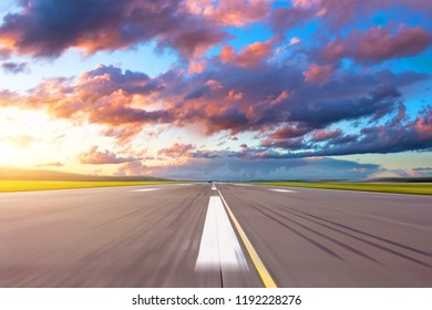 Runway at the airport in the evening sunset sun light bright red clouds
