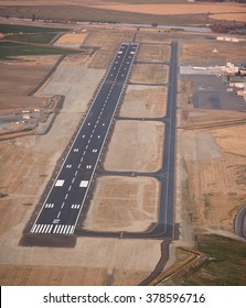 The runway, taxiway, terminal, and aircraft parking at small city airport, taken at dusk to show the landing lights and markings.