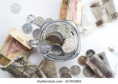 Rupiah Coin inside of Jar with money scatter around the jar