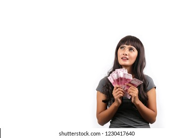 rupiah money holding indonesian women thinking with blank space.