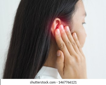 ruptured eardrum,tinnitus and meniere disease and otitis media in asian woman. She use hand touching her ear causes of ear pain on white background use for health care concept.