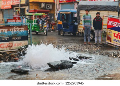A ruptured water pipe in the middle of the street in Haridwar. Rickshaws, cyclists and people bypass the scene of the accident. Crazy India. India, Haridwar, November 25, 2018.