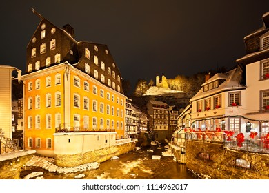 The Rur at the Red House (Rotes Haus) in the German Eifel village of Monschau during christmas time at night, the old castle ruin in the background, Germany.