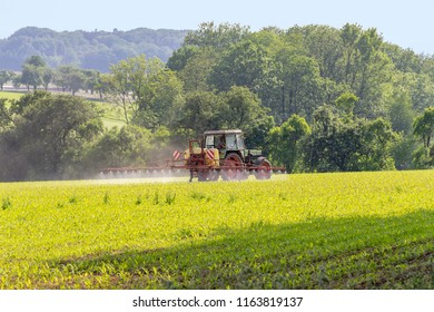 rural agricultural scenery with tractor apllying something on a field at spring time in Hohenlohe, a district in Southern Germany