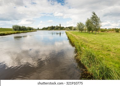Rural area with a wide canal closed with small yellow buoys on a rope and grass and trees on the banks. It's a sunny day in the summer season with beautiful clouds on a blue sky.