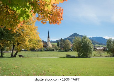 rural autumnal landscape spa town schliersee. view to the village church through colorful maple tree branches. sunny day in october.