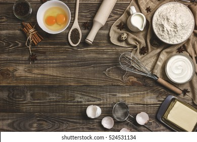 Rural background, cooking. The ingredients and kitchen items for baking cakes. Kitchen utensils, flour, eggs, dairy products, milk, cream, cooking appliances on a wooden background. Space for text