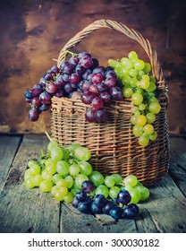 Rural Basket with Green and Red Grapes on Wooden Background. Country style