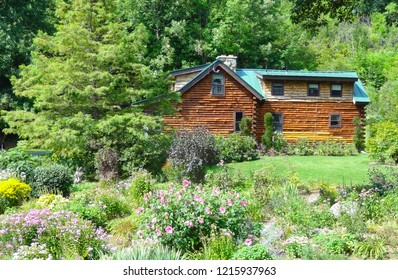 Rural brown log cabin nestled among trees and beautiful colorful flowers in the village of Bolton in Vermont